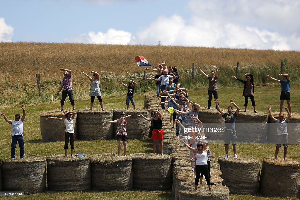 Fans cheer on riders as they wave from bales of straw during the 199 km and seventh stage of the 2012 Tour de France cycling race starting in...