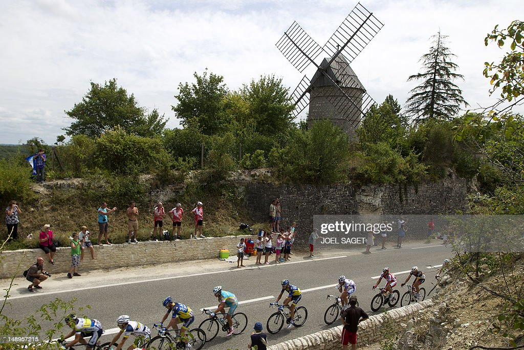 Fans cheer on the pack riding past a windmill in the 222,5 km and eighteenth stage of the 2012 Tour de France cycling race starting in Blagnac and finishing in Brive-la-Gaillarde, southwestern France, on July 20, 2012. AFP PHOTO / JOEL SAGET