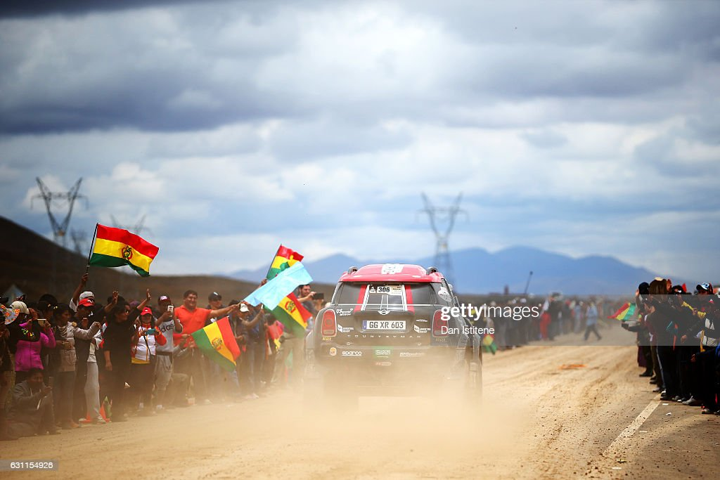 Fans cheer on Yazeed Al Rajhi of Saudi Arabia and Mini X-Raid and co-driver Timo Gottschalk of Germany in their John Cooper Works Rally Mini car as they depart the camp after stage six of the 2017 Dakar Rally between Oruro and La Paz was cancelled due to weather condtitons on January 7, 2017 in Oruro, Bolivia.