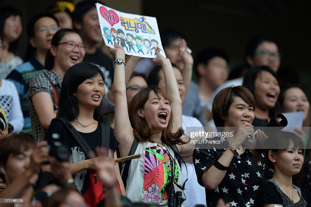Fans cheer players in the 2013 Asian Dream Cup charity football match at Hongkou stadium in Shanghai on June 23, 2013. Korean soccer star Park Ji Sung organises the annual Asian Dream Cup charity football match, with proceeds this year going to areas affected by the 2008 Sichuan earthquake. AFP PHOTO/Peter PARKS