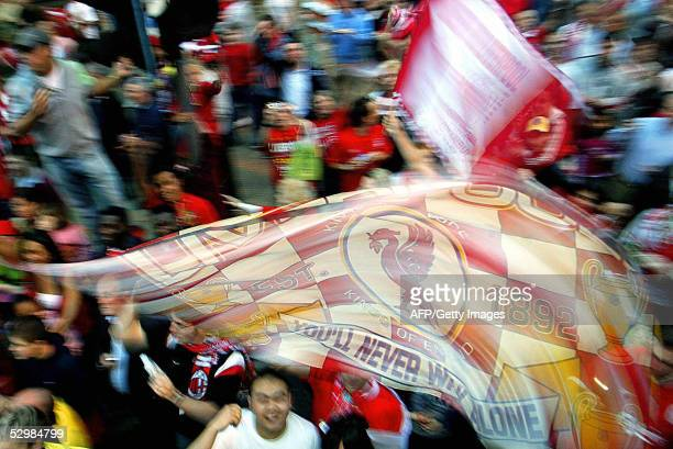 Fans cheer the Liverpool football team during a parade to welcome them home 26 May following their Champions League victory over AC Milan in Istanbul...