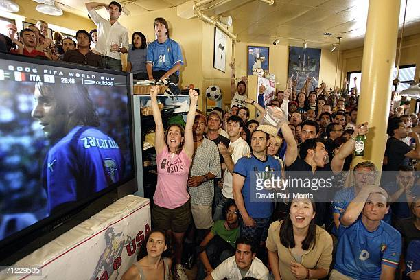 USA fans cheer when a USA free kick was knocked into the net by Italian defender Cristian Zaccardo as they watch the World Cup soccer match between...