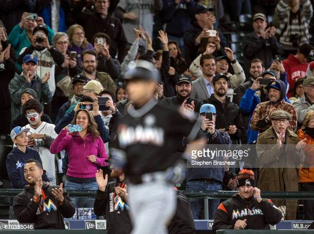 Fans cheers as Ichiro Suzuki of the Miami Marlins heads for home plate after hitting a solo home run off relieft pitcher Evan Marshall of the Seattle...