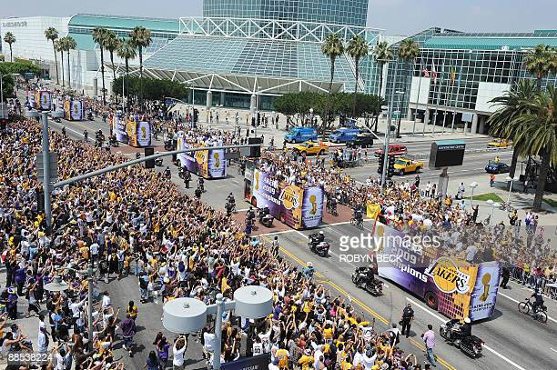 Fans cheers as The Los Angeles Lakers ride down the street on double decker buses during their 2009 NBA championship victory parade in downtown Los...