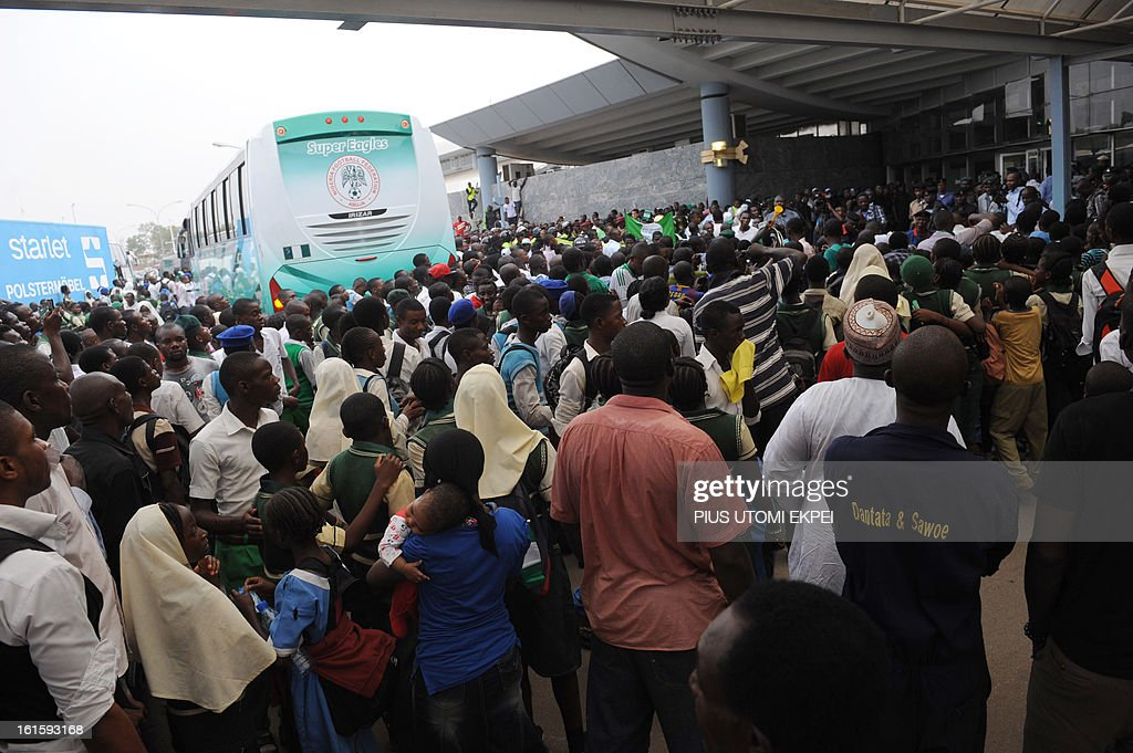 Fans cheers Nigerian football team as they arrive in Abuja on February 12, 2013. The newly crowned African champions Nigerian Super Eagles arrives in Abuja to a warm reception by fans and government officials after defeating Burkina Faso to win the 2013 African Cup of Nations in South Africa. AFP PHOTO/PIUS UTOMI EKPEI