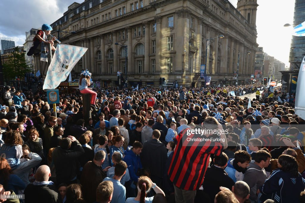 Fans climb on any available vantage point as Manchester City players parade the Barclays Premier League trophy in front of thousands of fans during their victory parade around the streets of Manchester on May 14, 2012 in Manchester, England.
