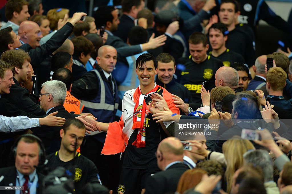 Fans congratulate Wigan Athletic's Austrian midfielder Paul Scharner (C) after his team won the English FA Cup final football match between Manchester City and Wigan Athletic at Wembley Stadium in London on May 11, 2013. Substitute Ben Watson scored an injury-time winner to give Wigan Athletic a sensational 1-0 win over Manchester City at Wembley Stadium on Saturday in the biggest FA Cup final upset in 25 years.