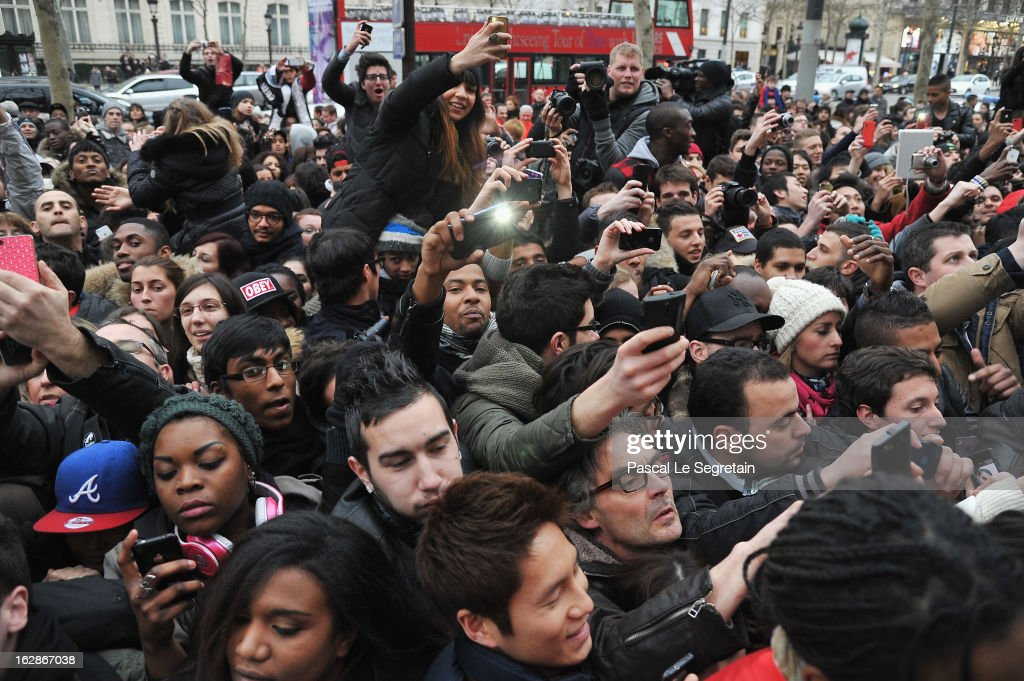 Fans crowd around as they try their best to catch a glimpse of David Beckham as he attends an autograph session at adidas Performance Store Champs-Elysees on February 28, 2013 in Paris, France.