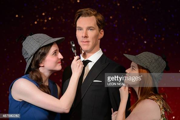 Fans Daisy England and Charlie Mitchell pose with Sherlock Holmesstyle deerstalker hats and a magnifying glass around the new wax figure of British...