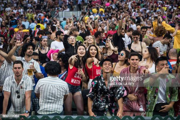 Fans dance during the final day of the Hong Kong Rugby Sevens tournament on April 9 2017 / AFP PHOTO / DALE DE LA REY