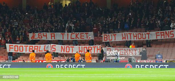 Fans display a banner against ticket prices during the UEFA Champions League match between Arsenal and Bayern Munich at The Emirates Stadium on...