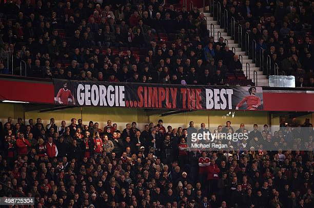 Fans display a banner as they remember former Manchester United player George Best during the UEFA Champions League Group B match between Manchester...