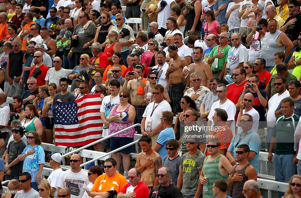 Fans display a flag during the National Anthem during the NASCAR Sprint Cup Series Camping World RV Sales 301 at New Hampshire Motor Speedway on July 14, 2013 in Loudon, New Hampshire.