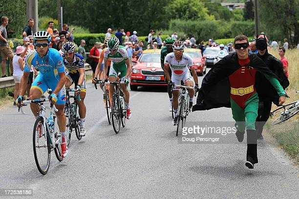 Fans dressed as Batman and Robin run alongside the riders including Yukiya Arashiro of Japan and Team Europcar during stage five of the 2013 Tour de...