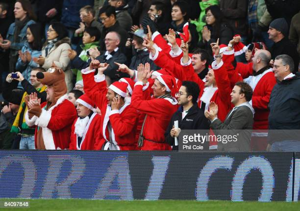 Fans dressed as Father Christmas cheer during the Barclays Premier League match between Fulham and Middlesbrough at Craven Cottage on December 20...
