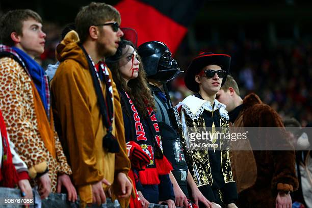 Fans dressed for a carnival watch the action from the stands during the Bundesliga match between Bayer Leverkusen and FC Bayern Muenchen at BayArena...