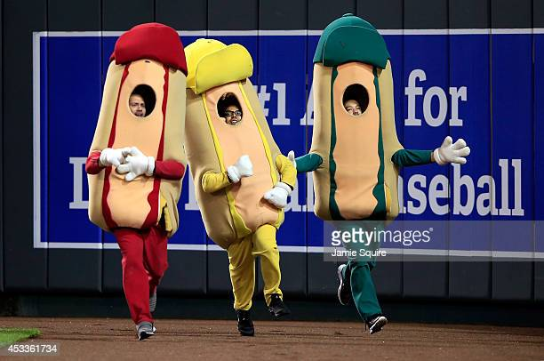 Fans dressed in costumes participate in a hot dog race during a break in the game between the San Francisco Giants and the Kansas City Royals at...