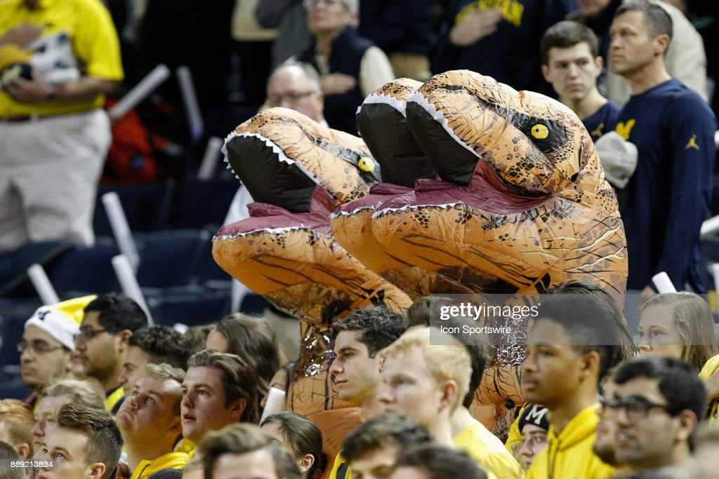 Fans dressed in inflatable T-Rex costumes sit in the Michigan student sections before the start of a regular season non-conference basketball game between the UCLA Bruins and the Michigan Wolverines on December 9, 2017 at the Crisler Center in Ann Arbor, Michigan. Michigan defeated UCLA 78-69 in overtime.