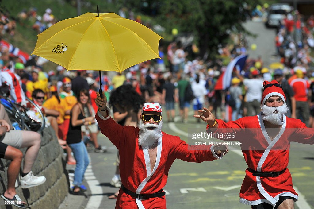 Fans dressed up as Christmas fathers pose with a Tour de France umbrella on July 19, 2009 during the 207,5 km and fifteenth stage of the 2009 Tour de France cycling race run between Pontarlier and Verbier (Switzerland). 2007 Tour de France winner and Kazakh cycling team Astana (AST)'s leader Alberto Contador of Spain won ahead of Danish cycling team Team Saxo Bank (SAX)'s leader Andy Schleck of Luxemburg and Italian cycling team Liquigas (LIQ)'s Vincenzo Nibali of Italy.