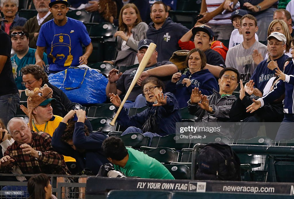 Fans duck out of the way of a flying bat let loose by Kyle Seager of the Seattle Mariners in the fifth inning against the Houston Astros at Safeco Field on September 9, 2013 in Seattle, Washington.