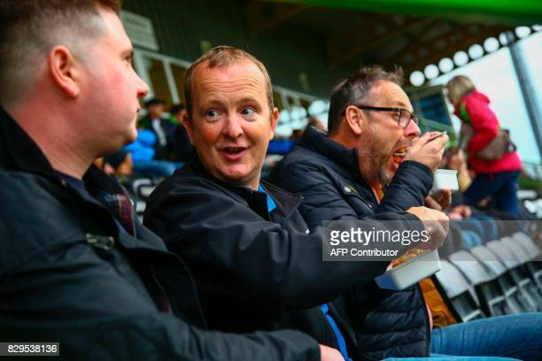 Fans eat vegan food in the stands ahead of the EFL Cup football match between Forest Green Rovers and MK Dons at The New Lawn stadium in Nailsworth...