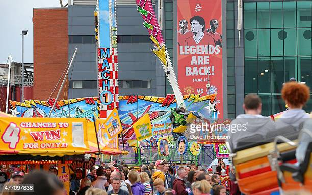 Fans enjoy the fairground set up outside the ground prior to the Manchester United Foundation charity match between Manchester United Legends and...