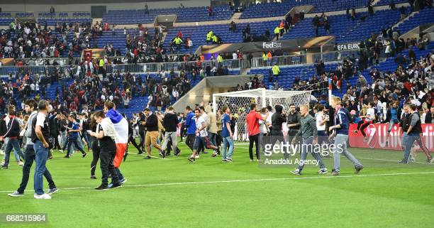 Fans enter the pitch after a fight breaks out in the tribune before the UEFA Europa League first leg quarter final football match between Olympique...