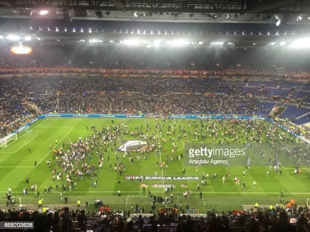 Fans enter the pitch before the UEFA Europa League first leg quarter final football match between Olympique Lyonnais and Besiktas JK at the Parc...