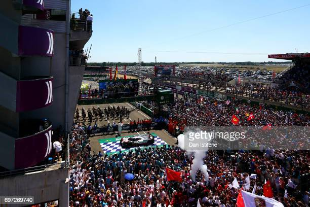 Fans fill the pit lane and pit straight as Earl Bamber Brendon Hartley and Timo Bernhard of the Porsche LMP Team celebrate on the podium with Vice...