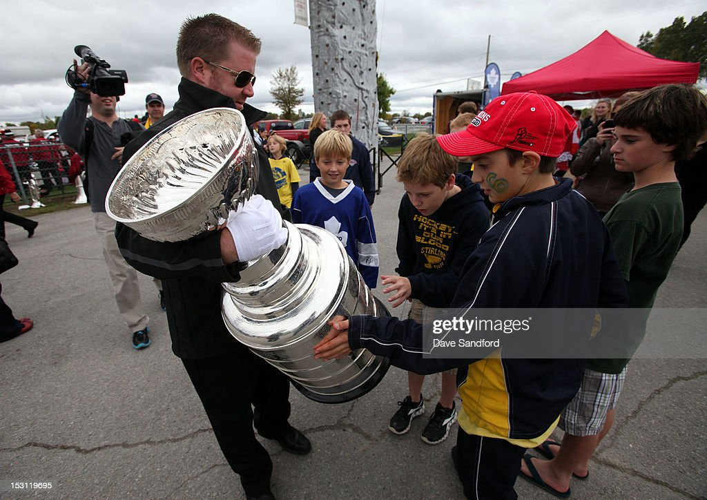 Fans gather around Mike Bolt of the Hockey Hall of Fame as he carries the Stanley Cup into the Fun Fair at the Stirling and District Recreation Centre during Kraft Hockeyville Day 1 on September 30, 2012 in Stirling, Ontario, Canada.