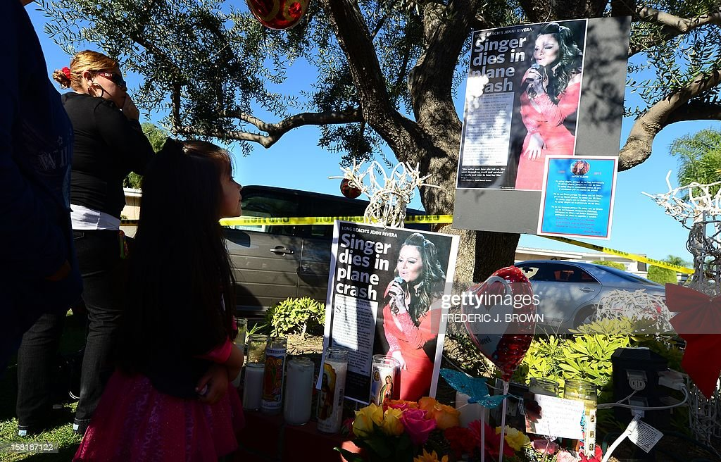 Fans gather in front of a makeshift shrine mourning the death of Mexican-American diva Jenni Rivera in front of her home in Lakewood, California on December 10, 2012, south of Los Angeles. Fans and celebrities are mourning the death of Rivera, a star on both sides of the border, as investigators scoured the site of her plane wreck for clues. The 43-year-old singer was among seven people, including two pilots, killed when their small Learjet plane crashed in rugged terrain in the northern Mexican state of Nuevo Leon early December 9. AFP PHOTO / Frederic J. BROWN