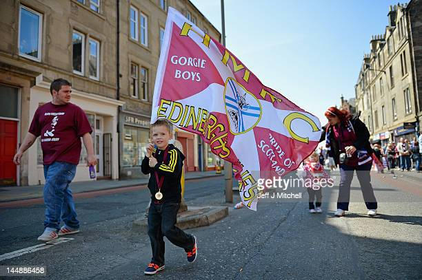 Fans gather to see Hearts players parade along Gorgie Road on an open top bus following their Scottish Cup final win over rivals Hibernian on May 20...
