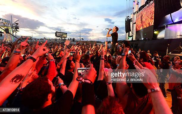 Fans gesture as they watch Rise Against fronted by lead singer Tim Mcllrath perform on day two of the 4day double weekend Rock in Rio USA 2015 music...