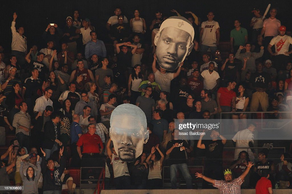 Fans get excited while holding up Lebron James and Chris Bosh signs during a game on December 6, 2012 at American Airlines Arena in Miami, Florida.