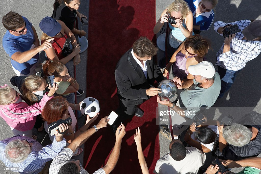 Fans Getting Autographs from Soccer Star