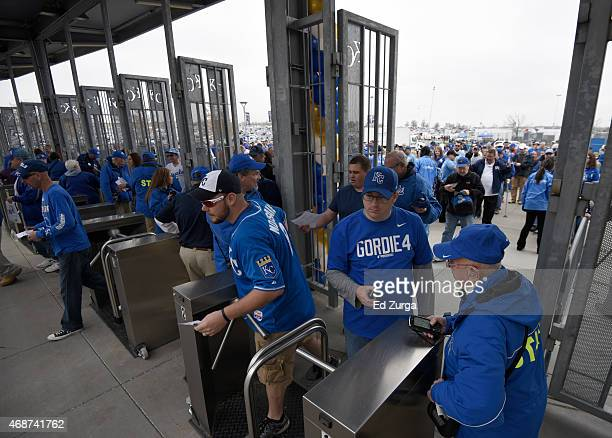 Fans go through the Kauffman Stadium turnstile as they head to their seats for the opening day game between the Chicago White Sox and Kansas City...