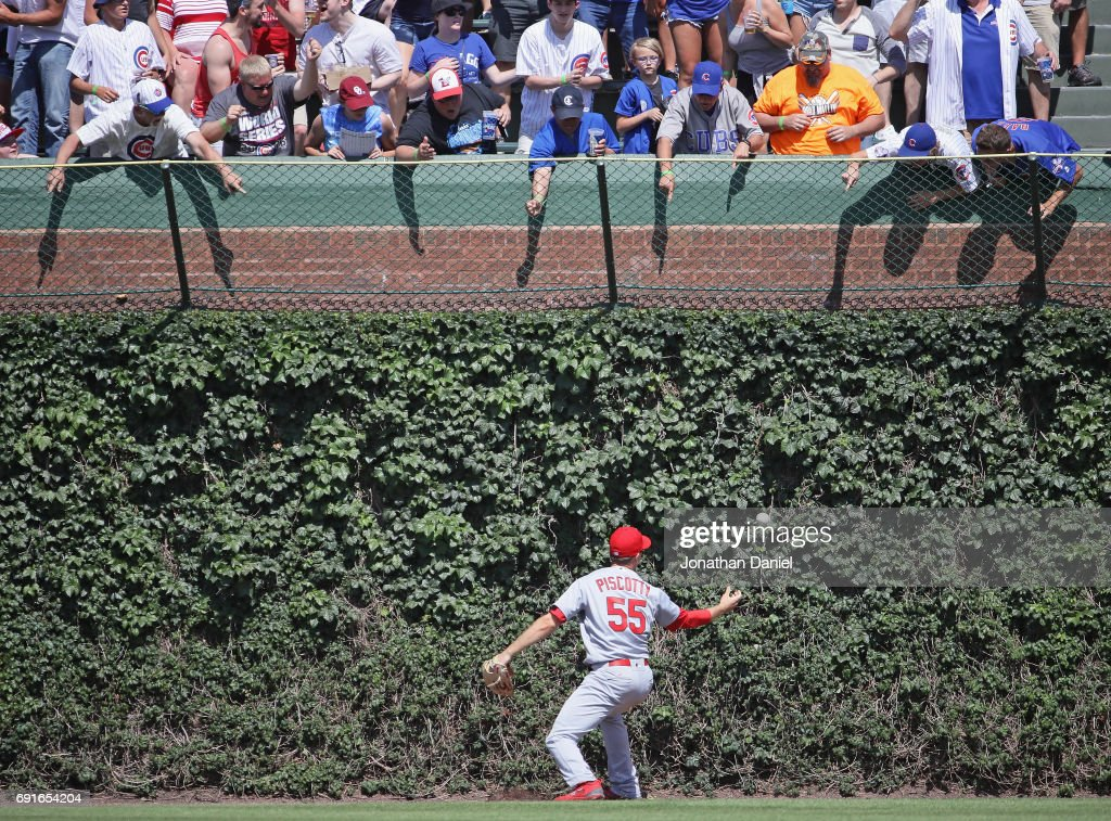 Fans harass Stephen Piscotty #55 of the St. Louis Cardinals as he misplays the ball on a double by Jason Heyward of the Chicago Cubs in the 6th inning at Wrigley Field on June 2, 2017 in Chicago, Illinois. The Cubs defeated the Cardinals 3-2.