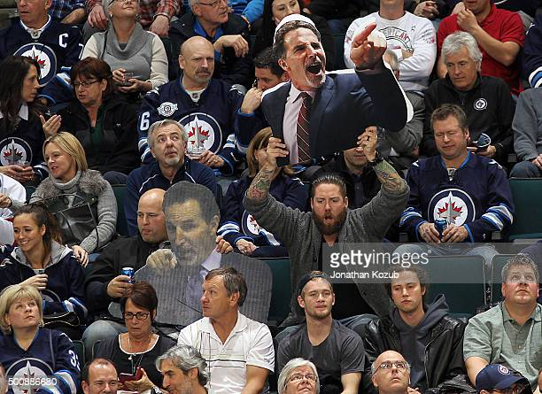 Fans hold aloft cardboard cutouts of Head Coach John Tortorella of the Columbus Blue Jackets during third period NHL action against the Winnipeg Jets...