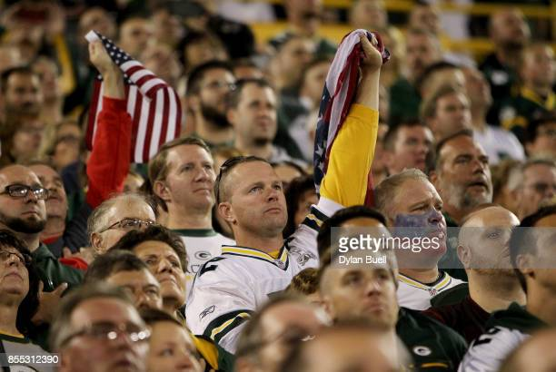 Fans hold American flags during the singing of the national anthem before the game between the Green Bay Packers and the Chicago Bears at Lambeau...