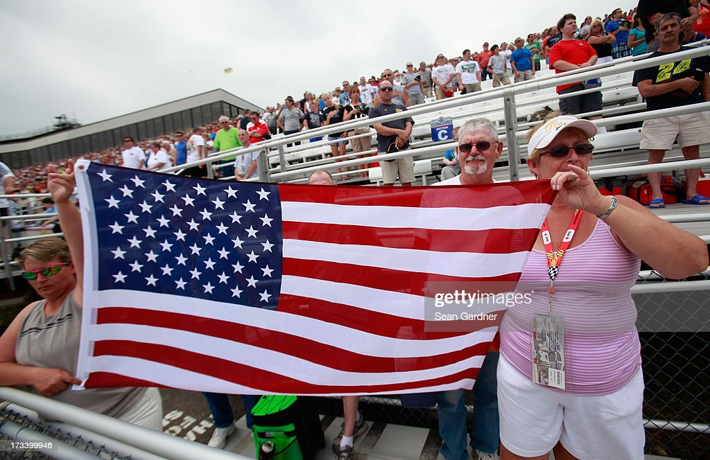 Fans hold an American flag prior to the NASCAR Whelen Modified Tour Town Fair Tire 100 at New Hampshire Motor Speedway on July 13, 2013 in Loudon, New Hampshire.