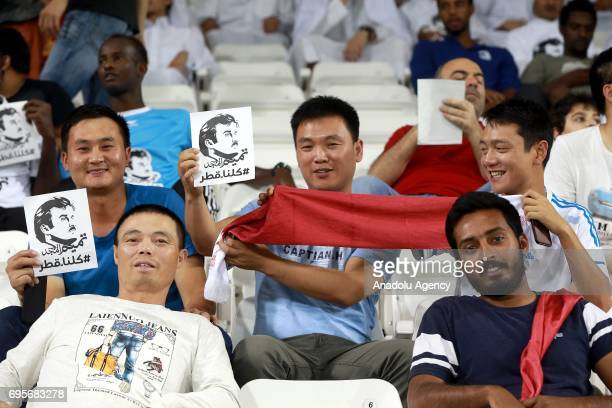 Fans hold banners of Emir of Qatar Tamim bin Hamad Al Thani during the 2018 FIFA World Cup Asian Qualifying group A football match between Qatar and...
