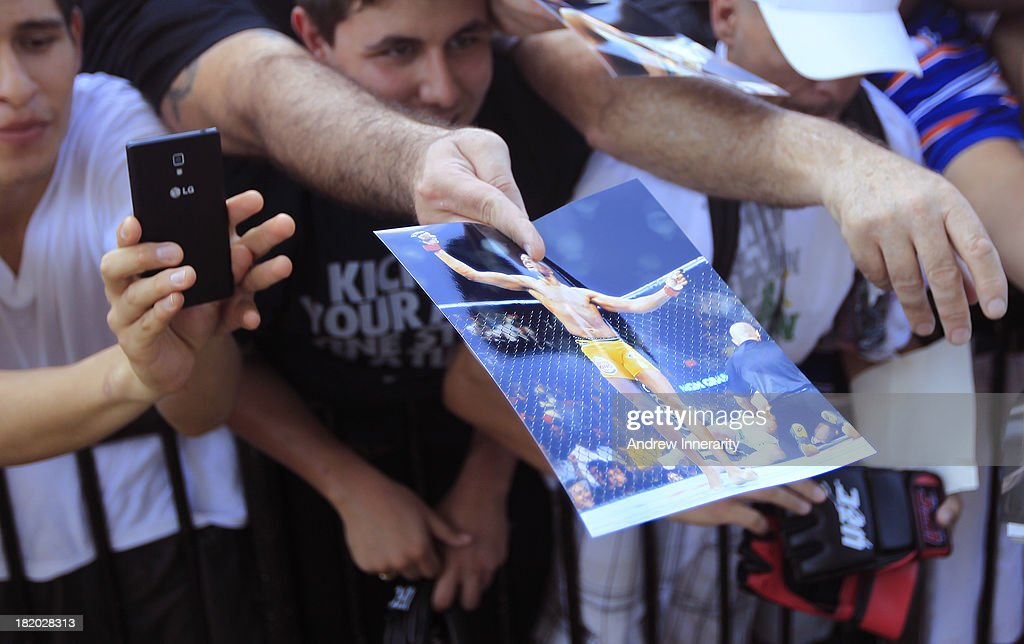 Fans hold material toward former middleweight champion Anderson Silva as he signs autographs during the UFC 168: Weidman v SIlva 2 press tour at Klipsch Amphitheater at Bayfront Park on September 27, 2013 in Miami, Florida.