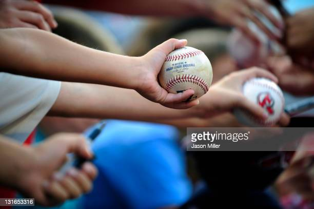 Fans hold out baseballs to be autographed prior to a game between the Cleveland Indians and the Detroit Tigers at Progressive Field on August 9 2011...