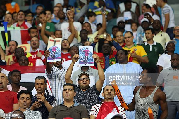 Fans hold photos of former footballer Mohamed Aboutrika during the African Cup of Nations 2017 Group D football match between Egypt and Uganda at...