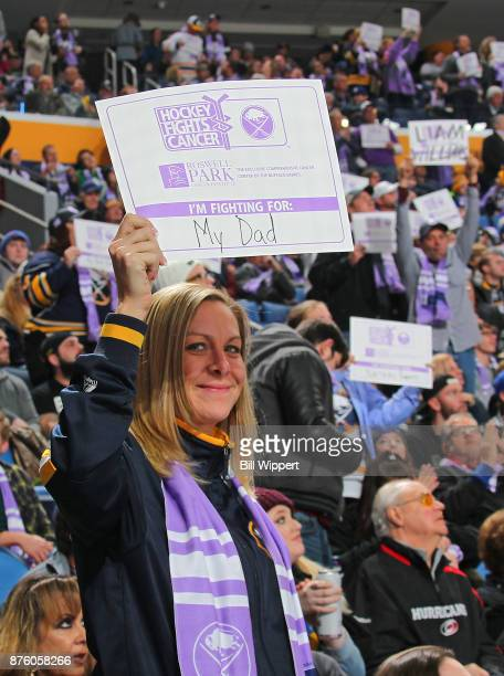 Fans hold placards proclaiming who they are fighting for on Hockey Fights Cancer Night during an NHL game between the Buffalo Sabres and the Carolina...