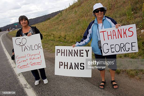 Fans hold signs in support of riders Taylor Phinney and George Hincapie during stage one of the USA Pro Challenge from Durango to Telluride on August...