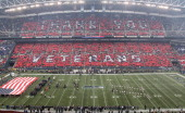 Fans hold signs spelling out 'Thank You Veterans' prior to the game between the Seattle Seahawks and the Baltimore Ravens at CenturyLink Field on...
