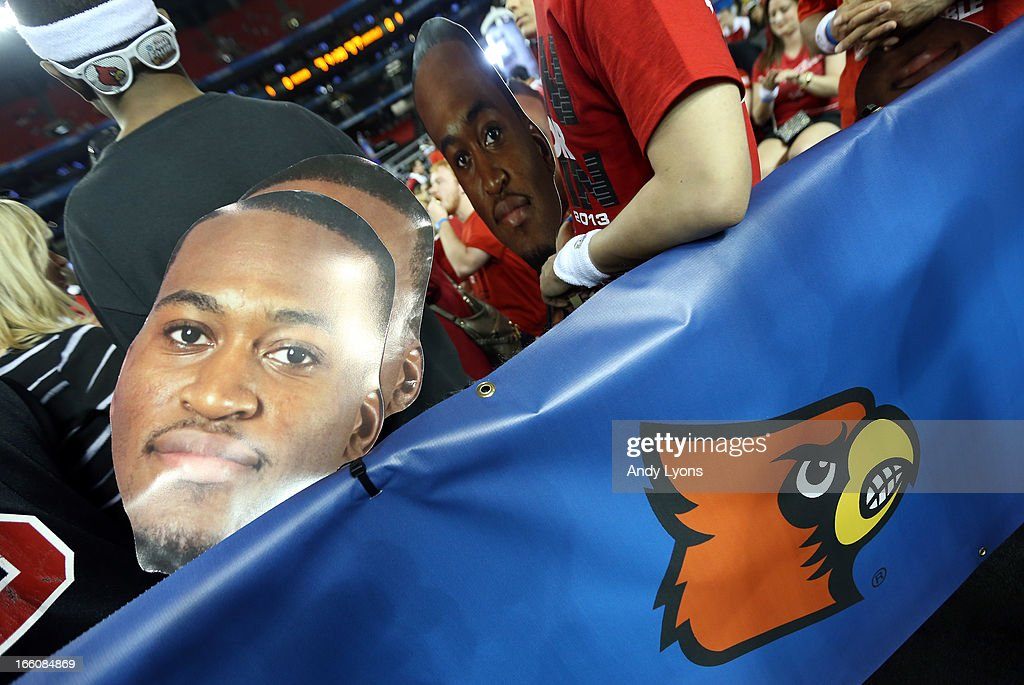 Fans hold signs with the likemess of injured guard Kevin Ware #5 of the Louisville Cardinals against the Michigan Wolverines during the 2013 NCAA Men's Final Four Championship at the Georgia Dome on April 8, 2013 in Atlanta, Georgia.