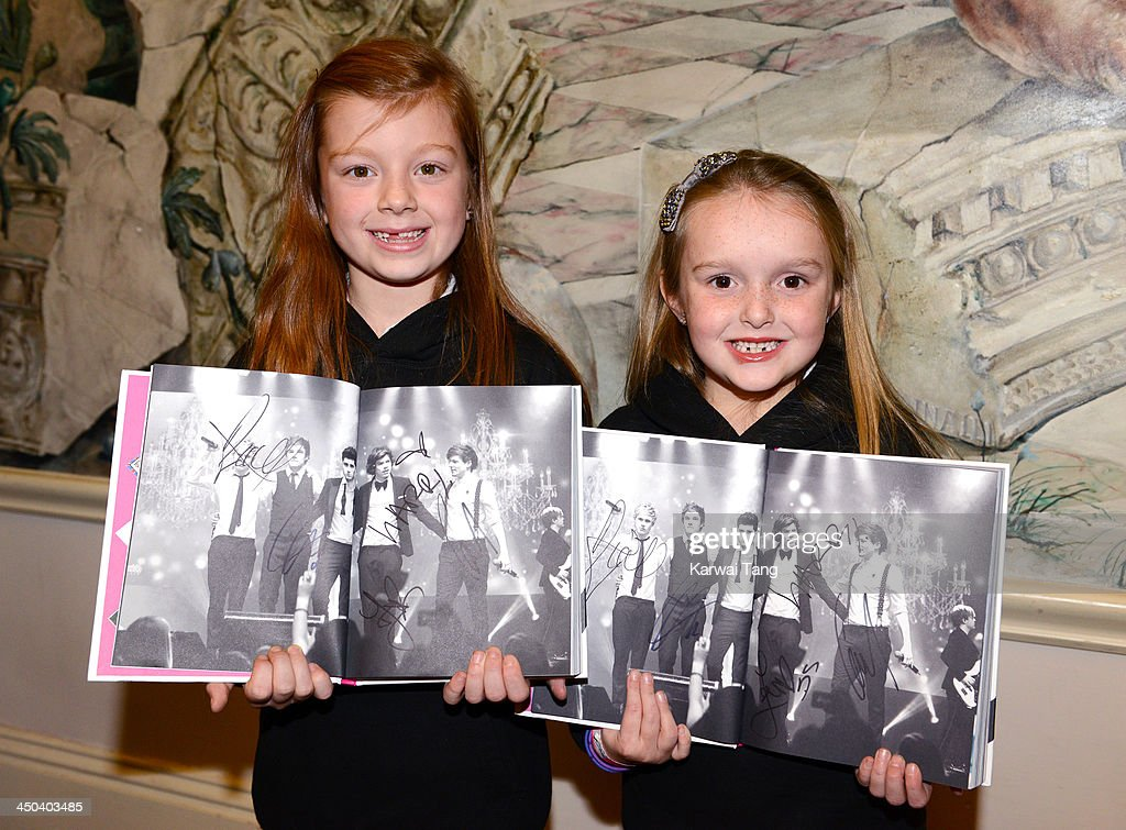 Fans hold their signed books as they attend the book signing of One Direction's new book 'Where We Are' held at Alexandra Palace on November 18, 2013 in London, England.