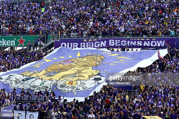 Fans hold up a flag prior to the inaugural MLS soccer match between the New York City FC and the Orlando City SC at the Orlando Citrus Bowl on March...